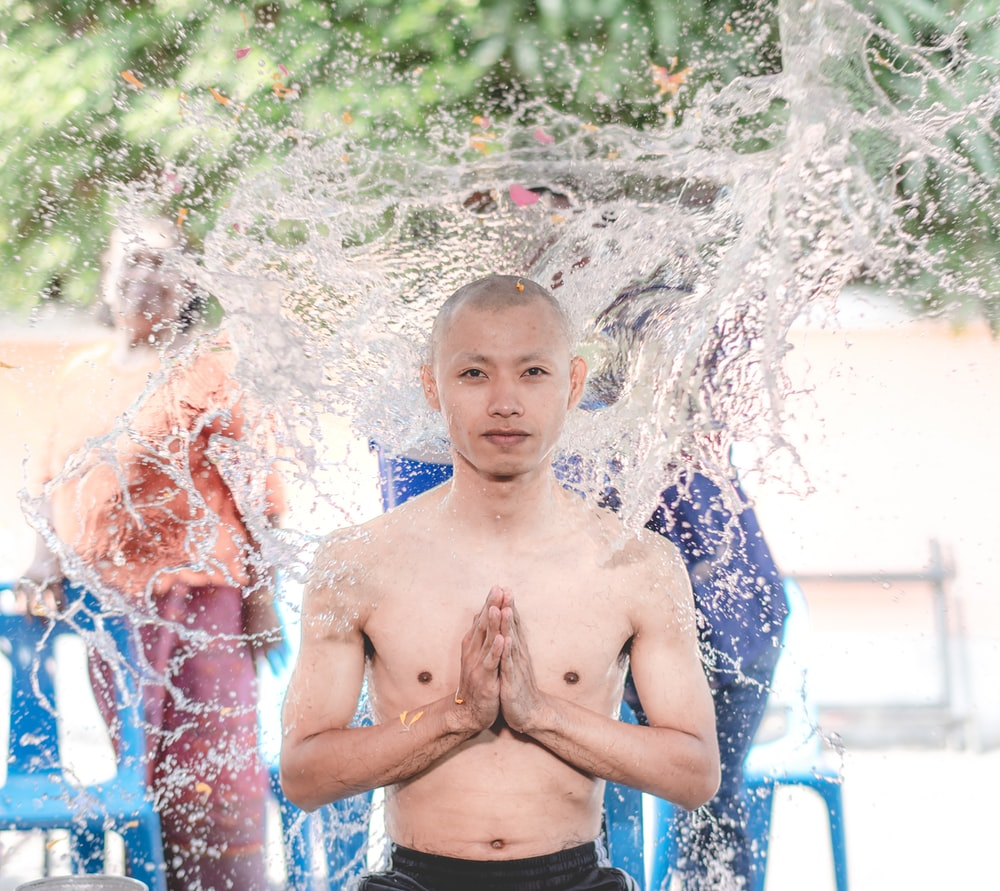topless boy in blue shorts standing on water fountain during daytime