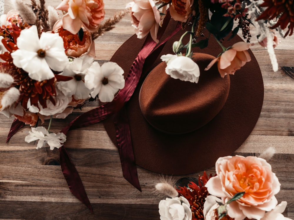 brown fedora hat beside white and pink flowers