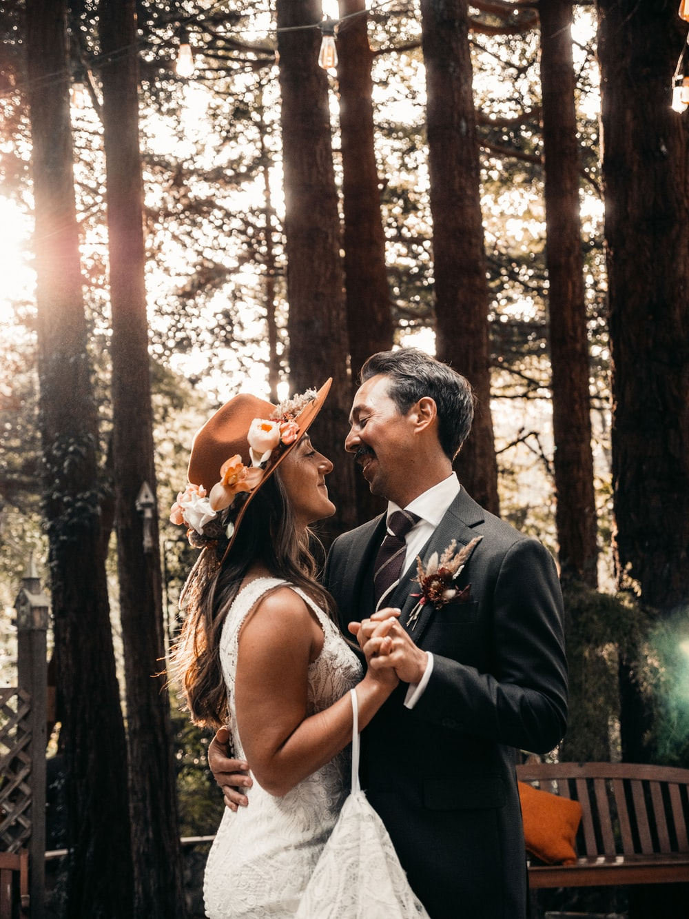 man in black suit jacket kissing woman in white sleeveless dress