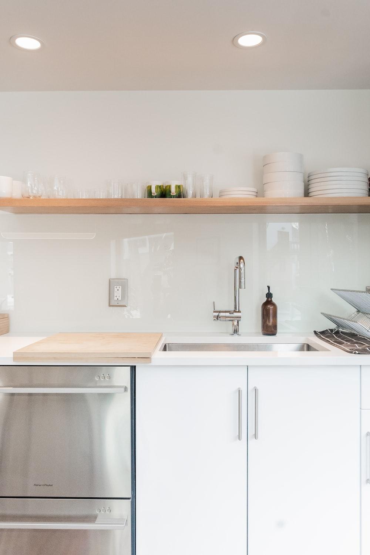 white ceramic plates on white wooden kitchen cabinet
