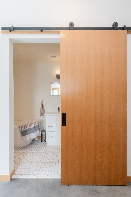 brown wooden door near white ceramic toilet bowl