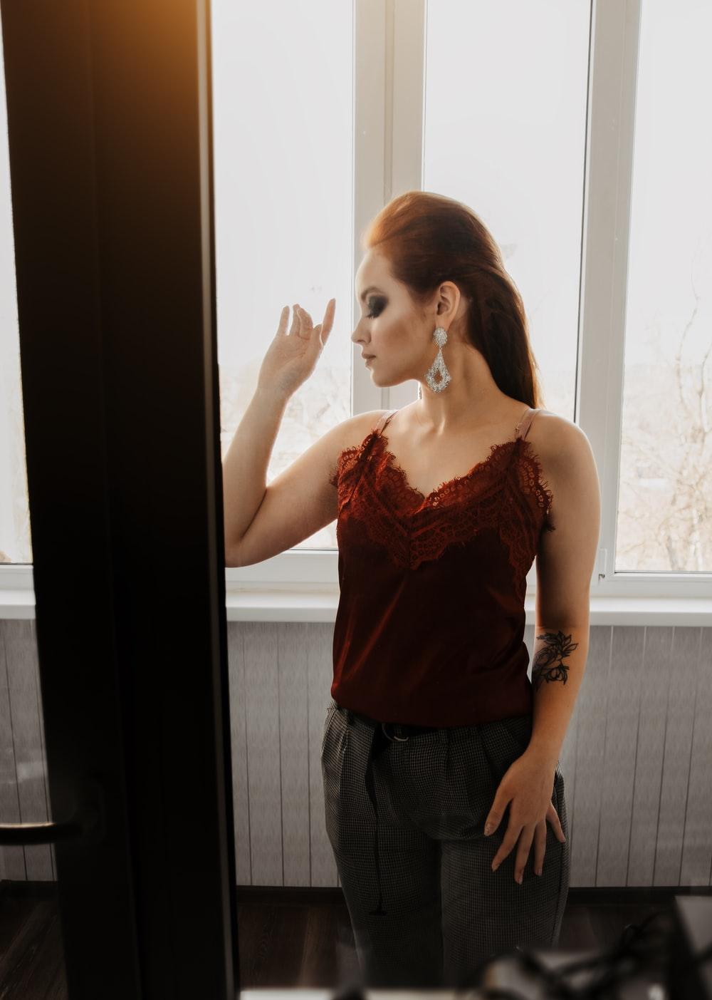 woman in red spaghetti strap top and black denim jeans standing beside glass window