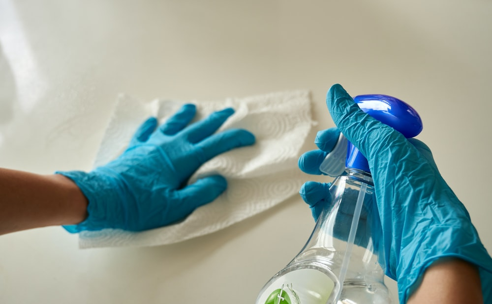 person holding blue textile near clear glass bottle