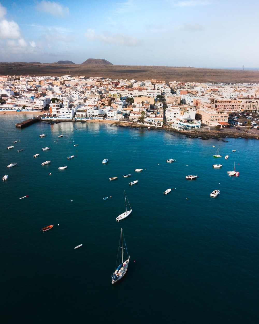 aerial view of boats on sea near city during daytime