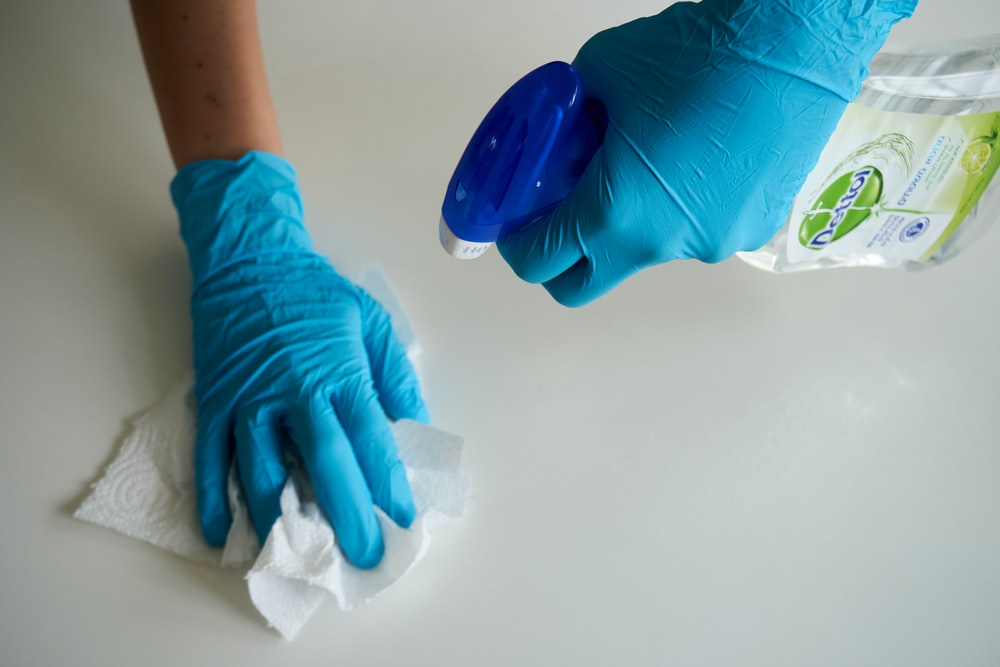 person in blue gloves holding white textile