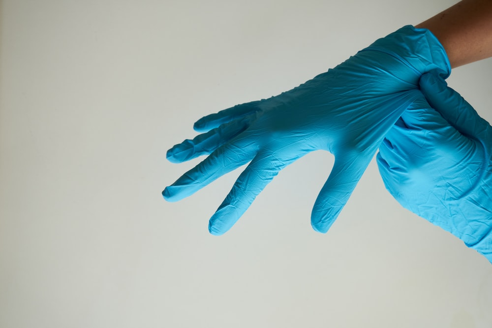 hands putting on latex gloves