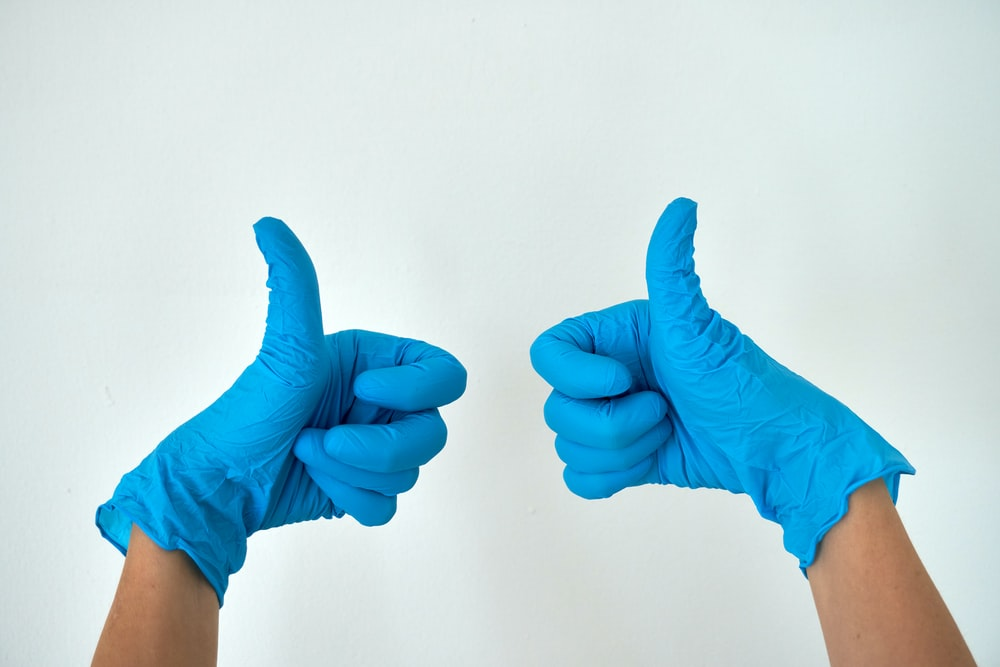 person wearing blue gloves holding hands