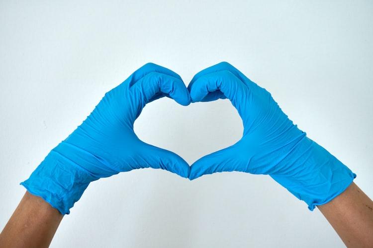 gloved hands making heart