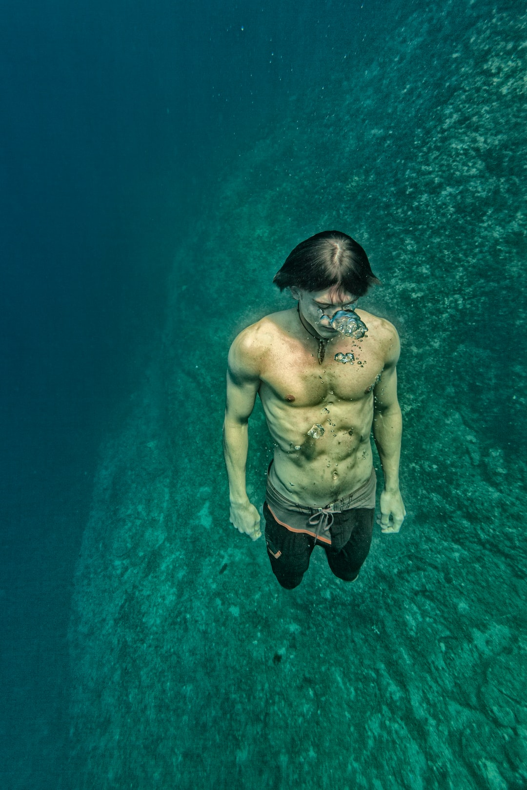 Shirtless Man submerged Underwater with air bubbles.