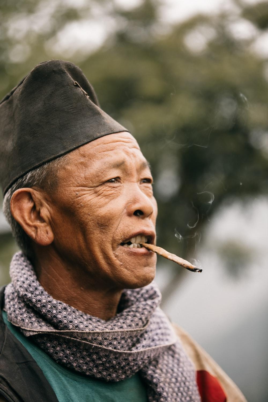 man smoking cigarette wearing black knit cap