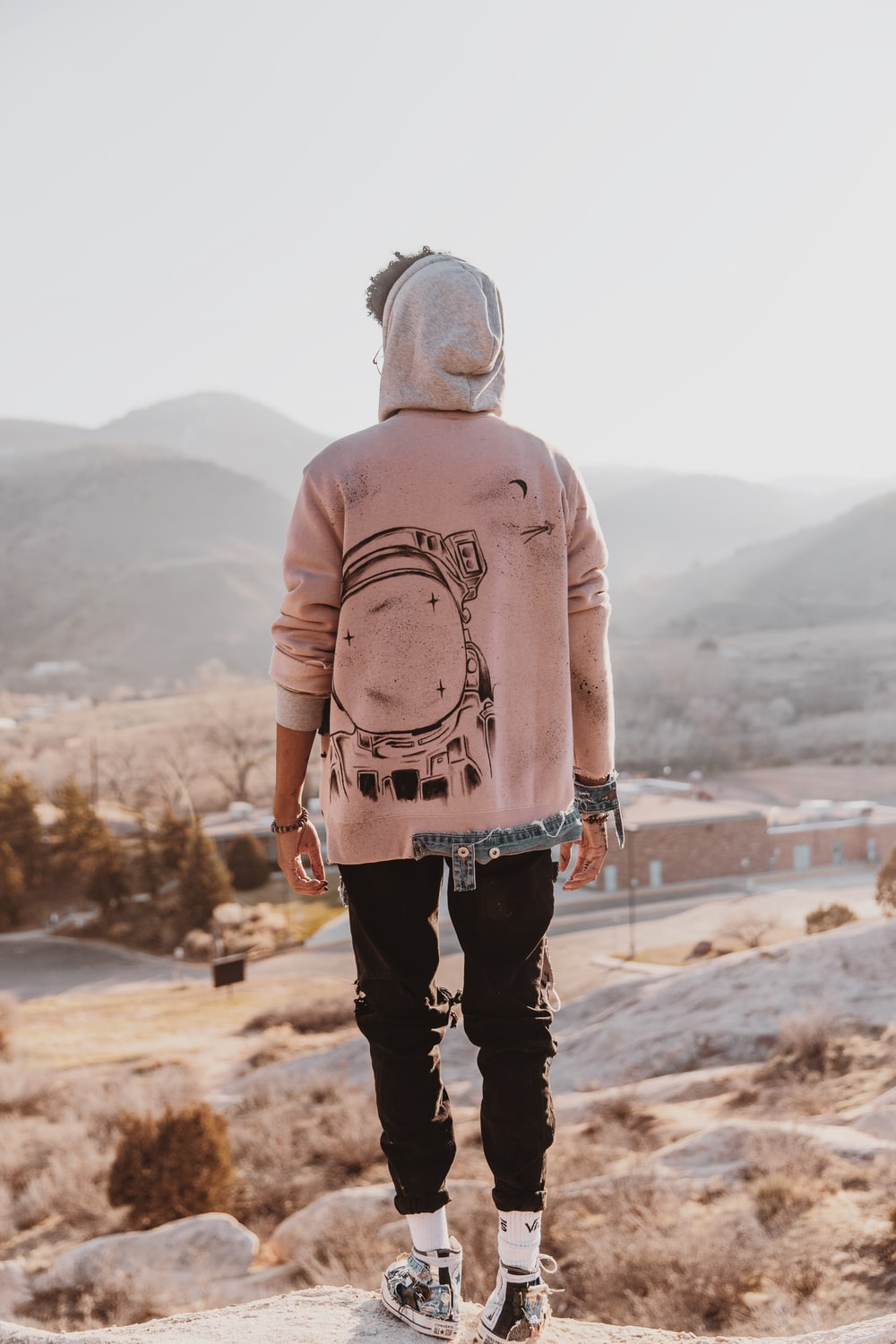 man in pink sweater and black pants standing on brown sand during daytime
