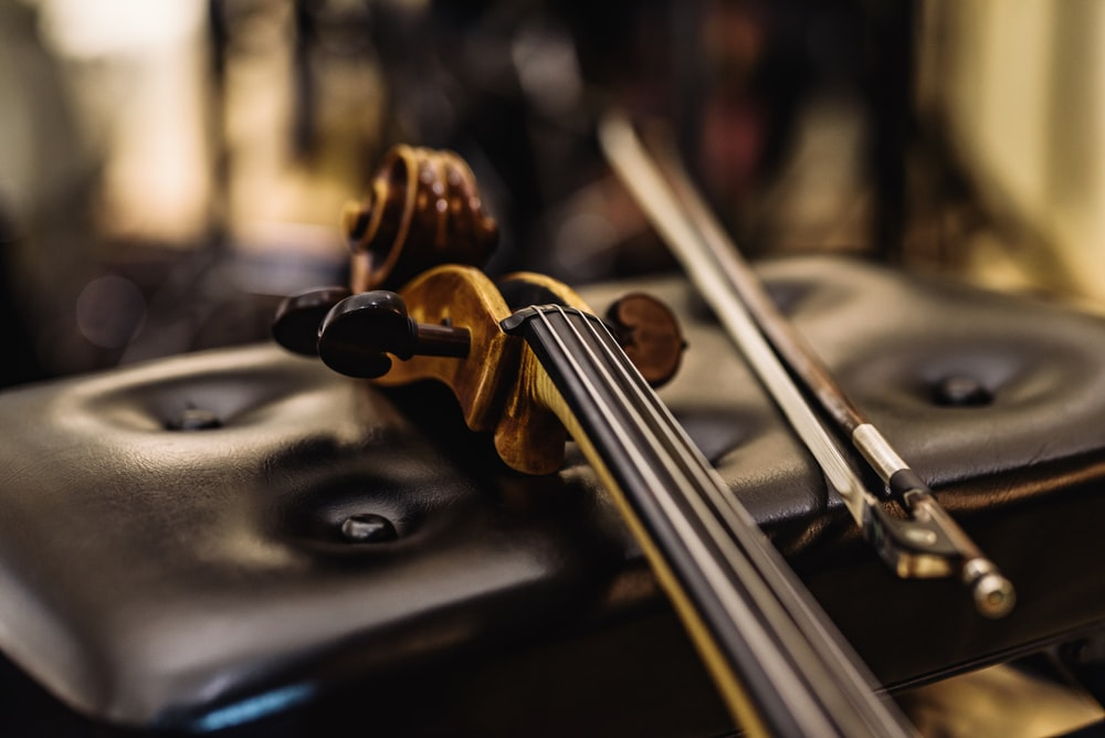 brown wooden violin on black leather textile