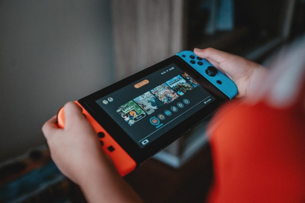 person holding black and orange nintendo switch
