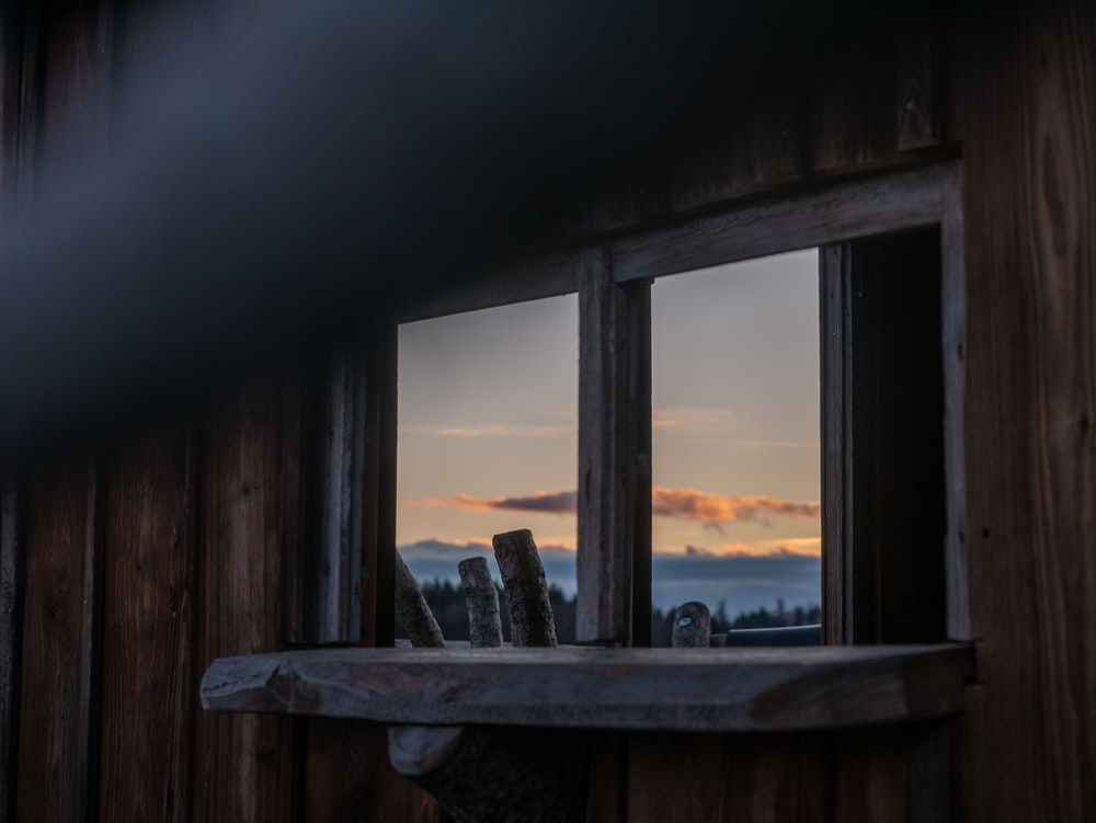 brown wooden bench near window during sunset