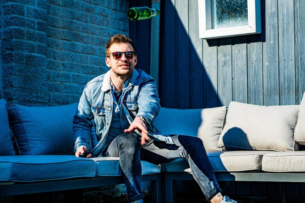 man in blue denim jacket and black pants sitting on bench