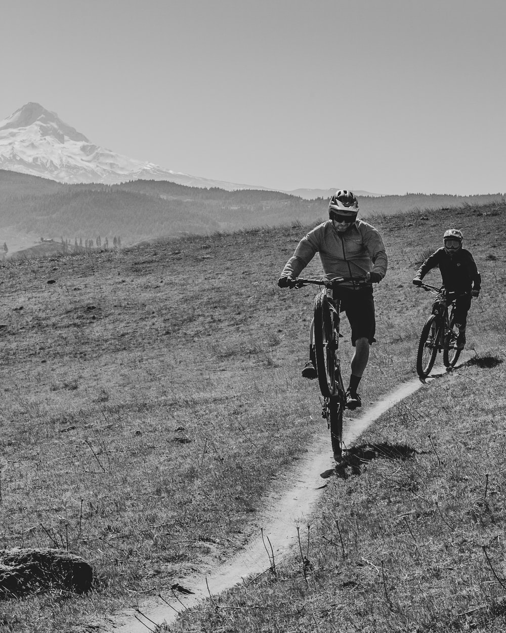 grayscale photo of 2 men riding bicycle on road