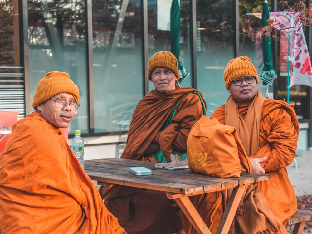 2 men in orange thobe sitting on brown wooden bench during daytime