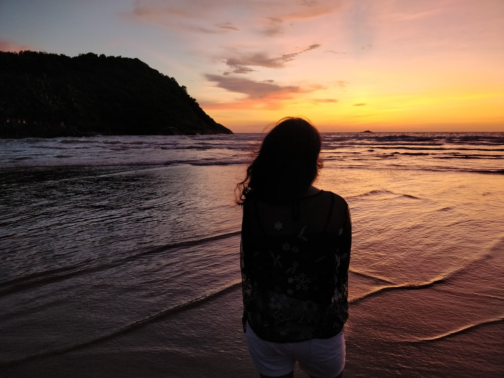 woman in black jacket and white shorts standing on beach during sunset