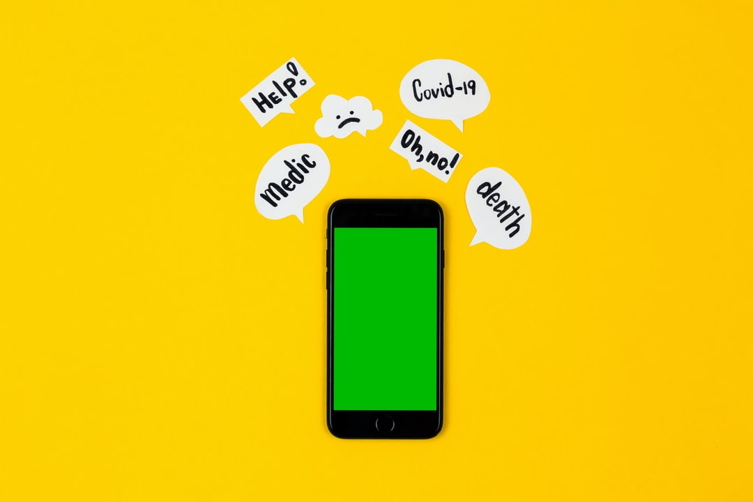 Creative concept of coronavirus mockup. A black telephone lies on a yellow background, next to it are paper message clouds on which the inscriptions associated with the covid-19 virus are written