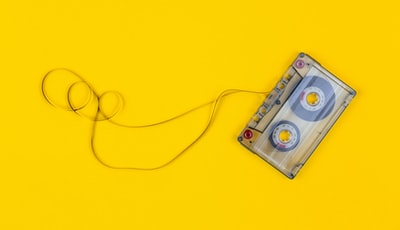 Top view of audio cassette with tangled tape on bright yellow background with copy space, minimalistic composition