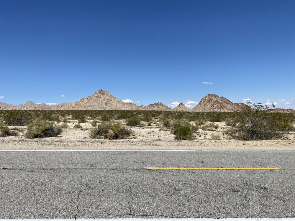 gray asphalt road near brown mountain under blue sky during daytime