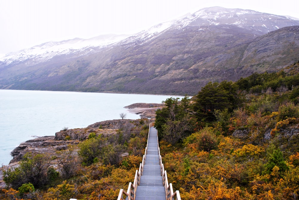 white wooden bridge on lake near green mountains during daytime