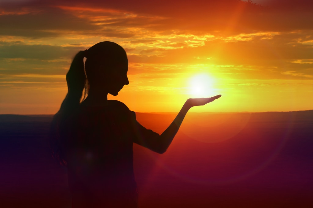 silhouette of woman raising her right hand during sunset