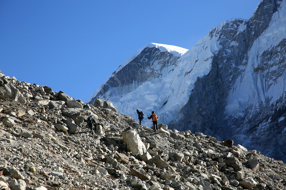 person in black jacket and black pants standing on rocky mountain during daytime