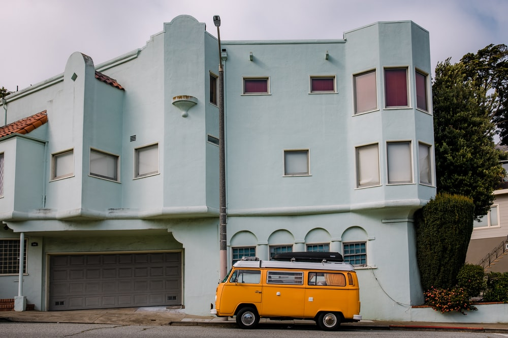 yellow and black van parked beside white concrete building during daytime
