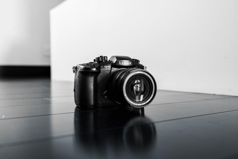 black nikon dslr camera on blue table