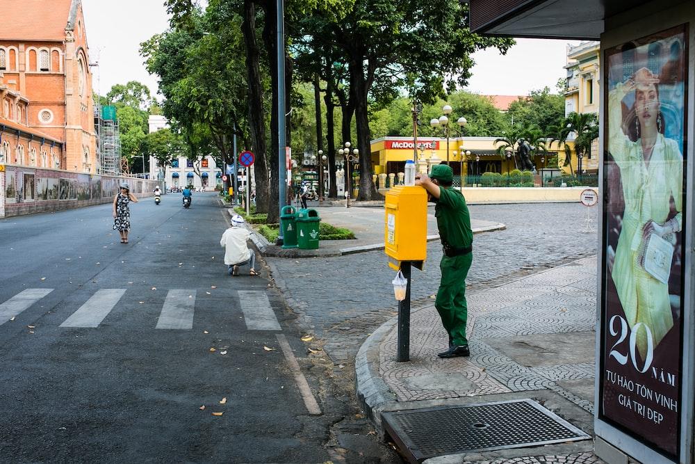 man in green jacket and gray pants walking on sidewalk during daytime