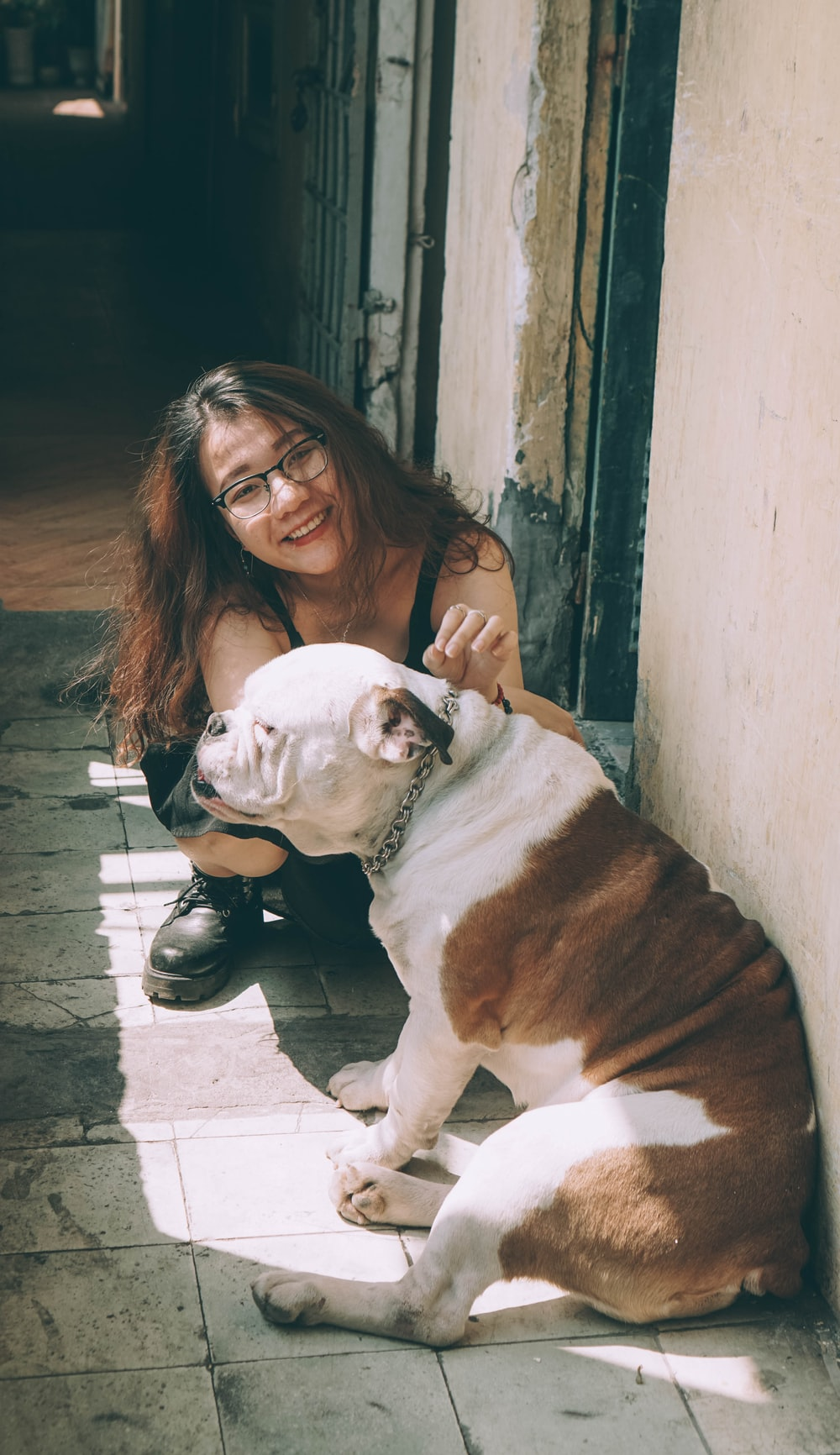 woman in black leather jacket hugging white and brown short coated dog