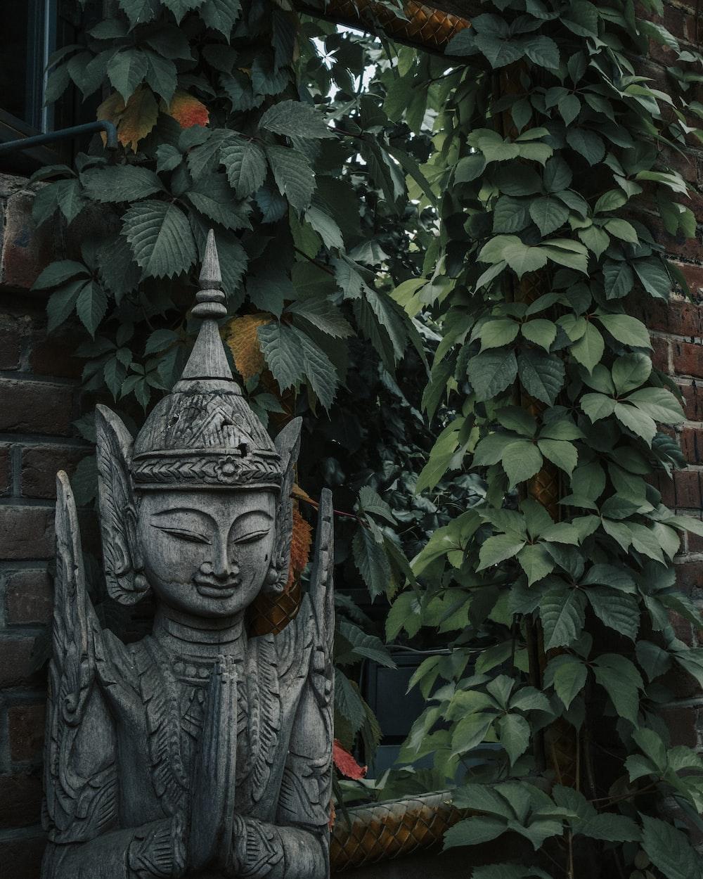 gray concrete statue near green plant