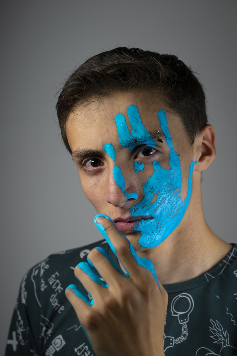 woman in black and white crew neck shirt with blue face paint