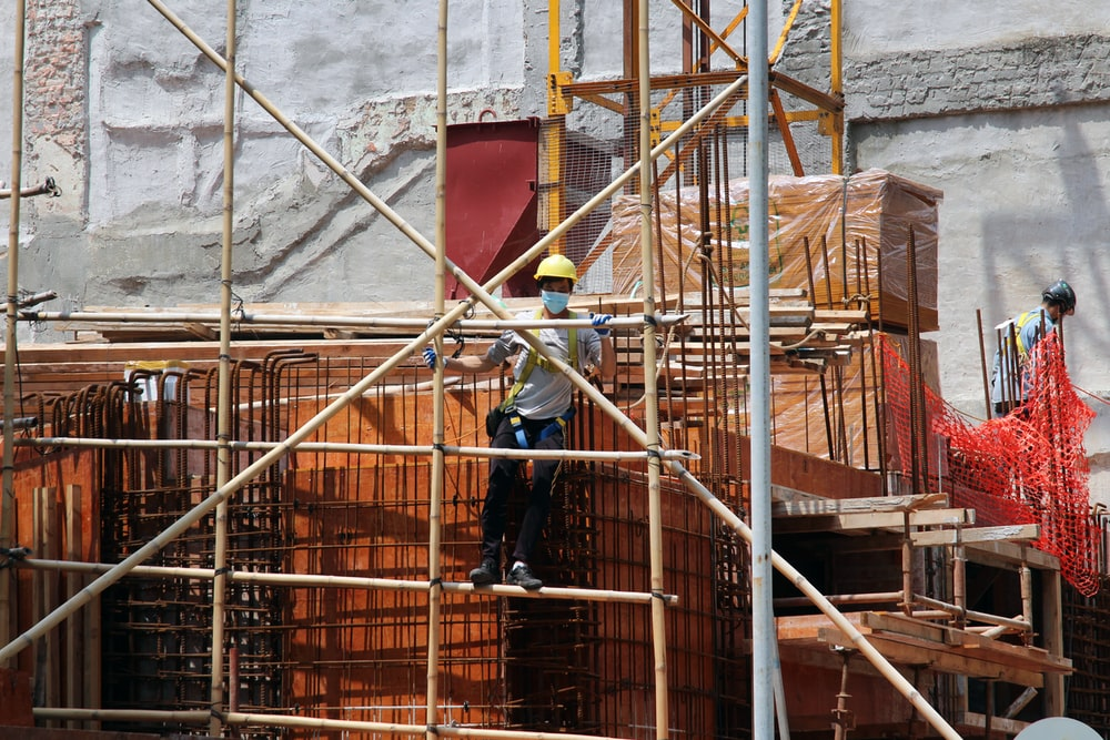 man in black jacket and blue denim jeans standing on brown metal ladder during daytime