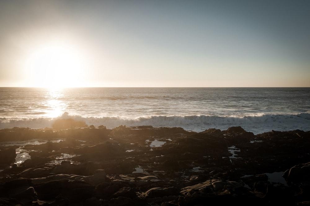 sea waves crashing on rocks during sunset