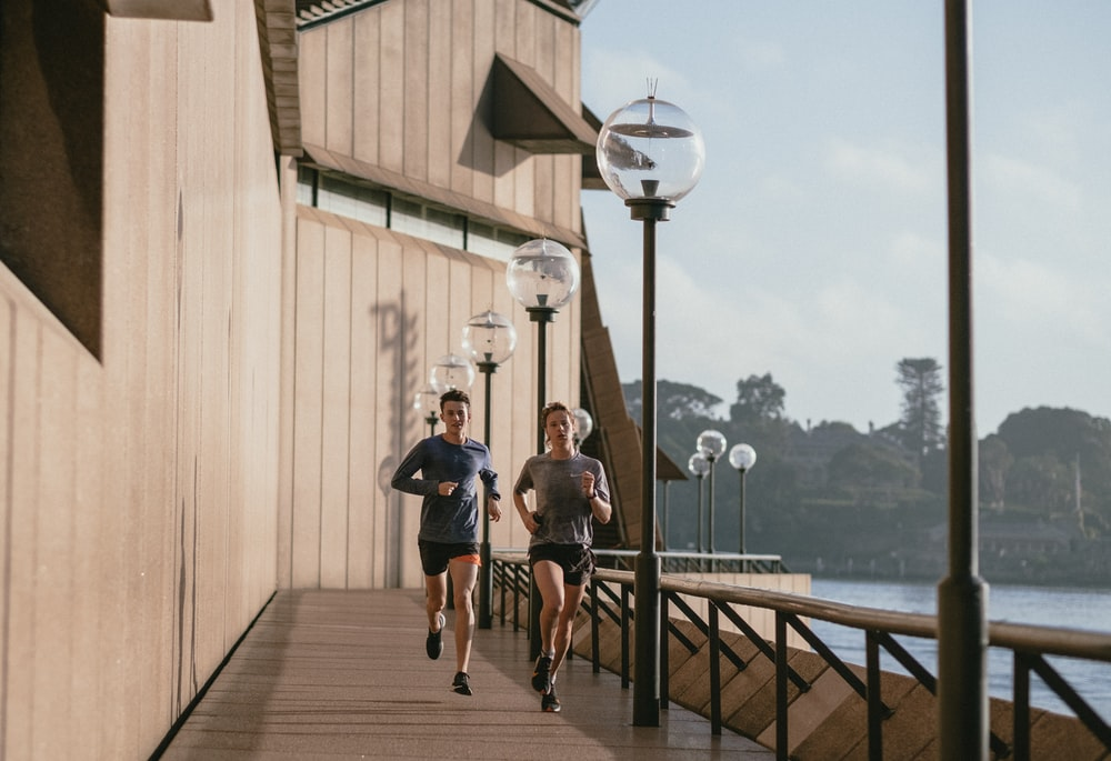 man in black t-shirt and blue shorts running on brown wooden dock during daytime
