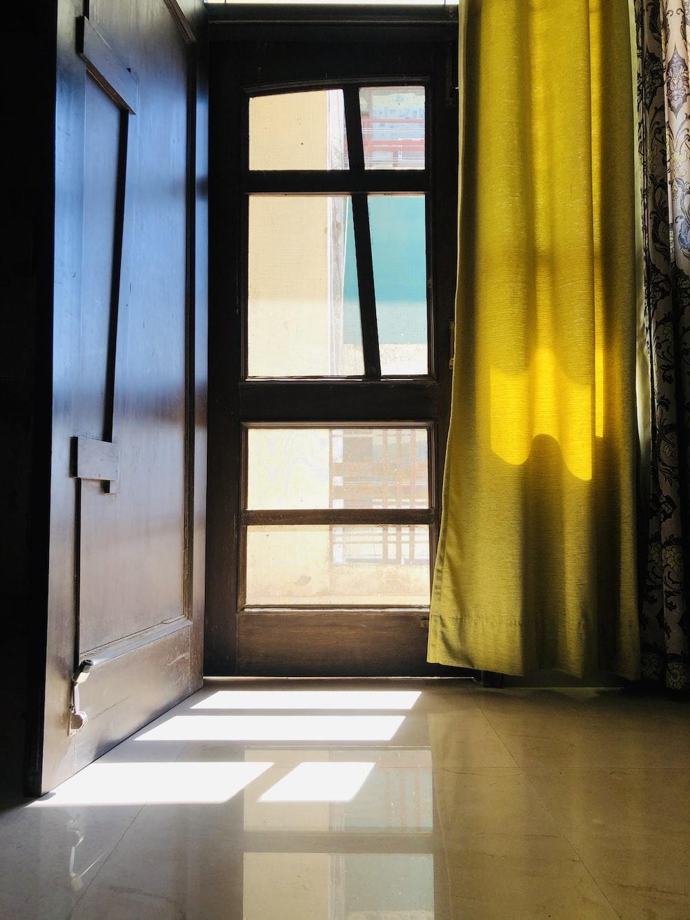 brown wooden door with yellow curtain