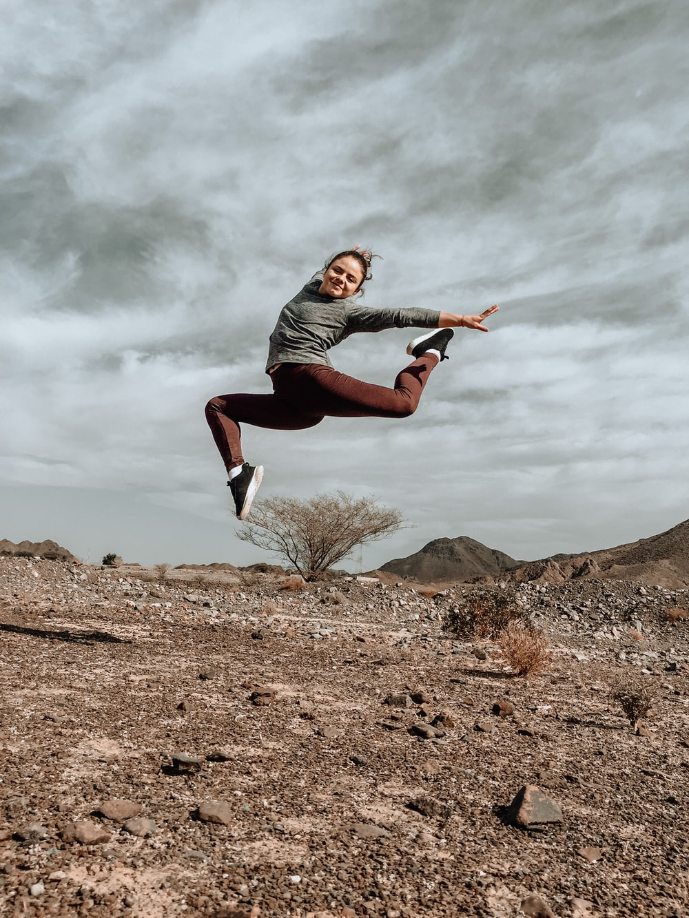 woman in gray long sleeve shirt and black pants jumping on brown rock during daytime