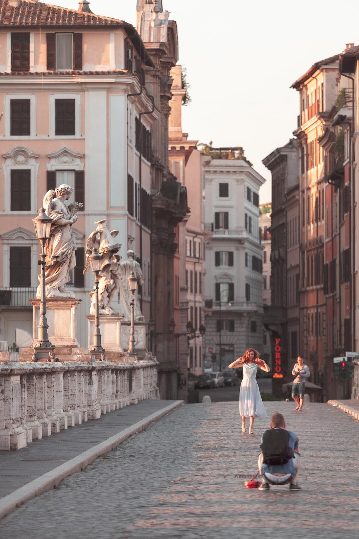 people walking on street near white concrete building during daytime