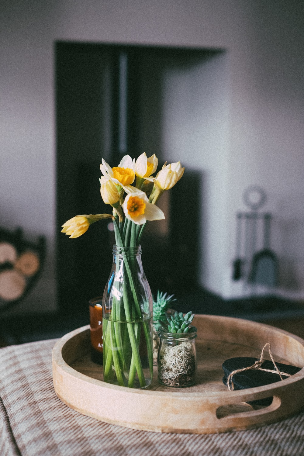 yellow daffodils in clear glass vase on brown wooden table