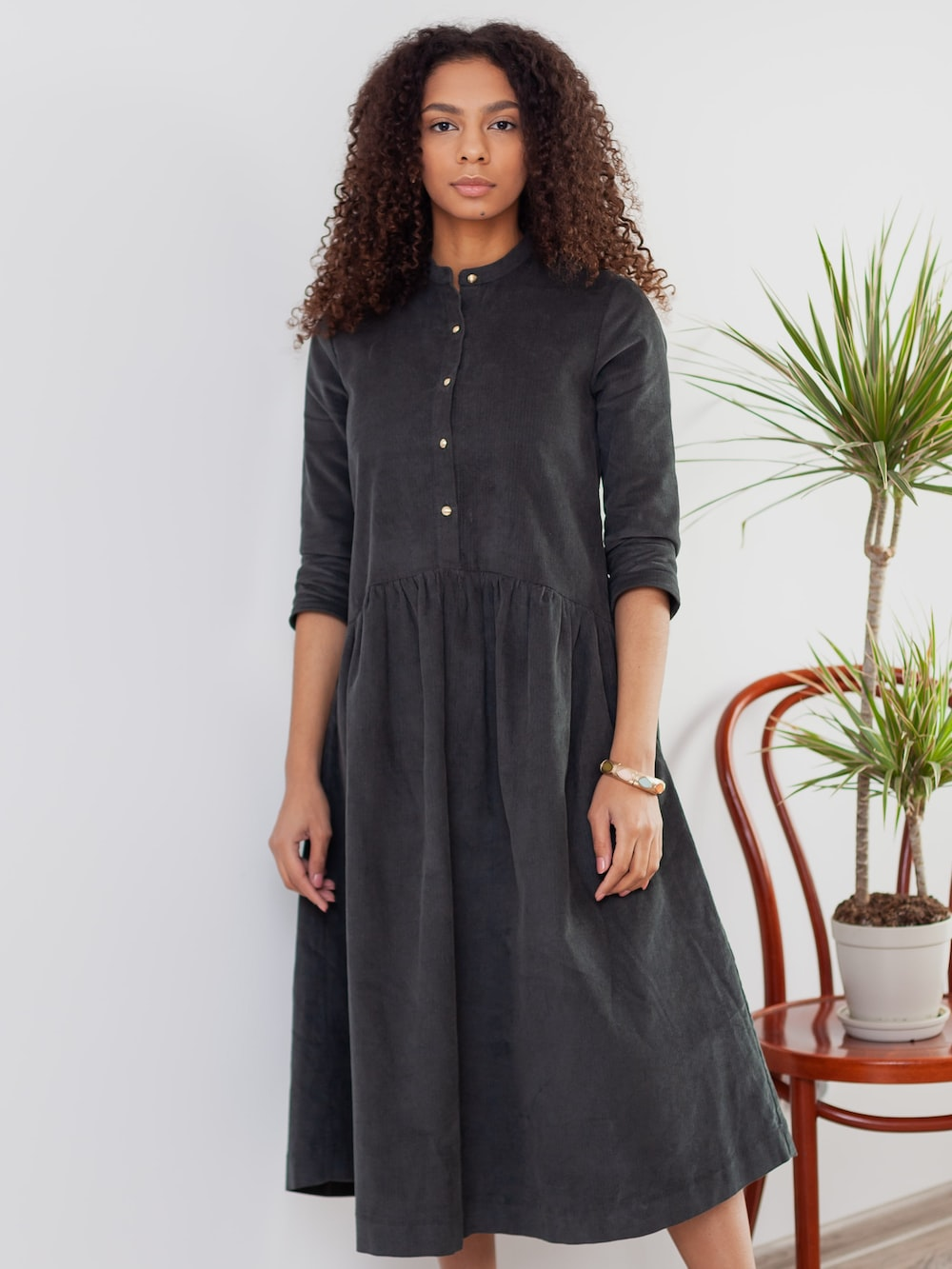 woman in black button up dress standing near green plant