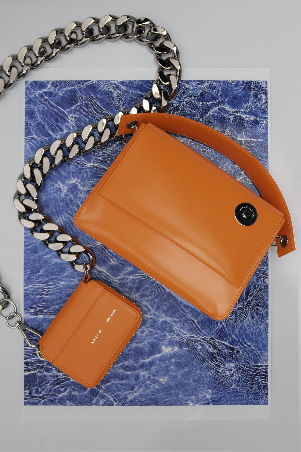 brown leather sling bag on blue and white textile