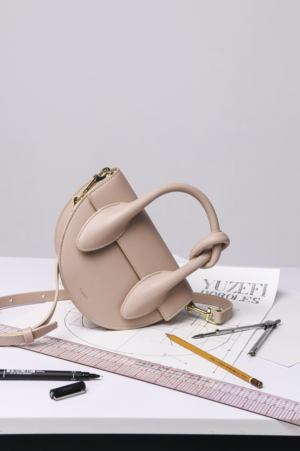 brown leather handbag on white ruled paper