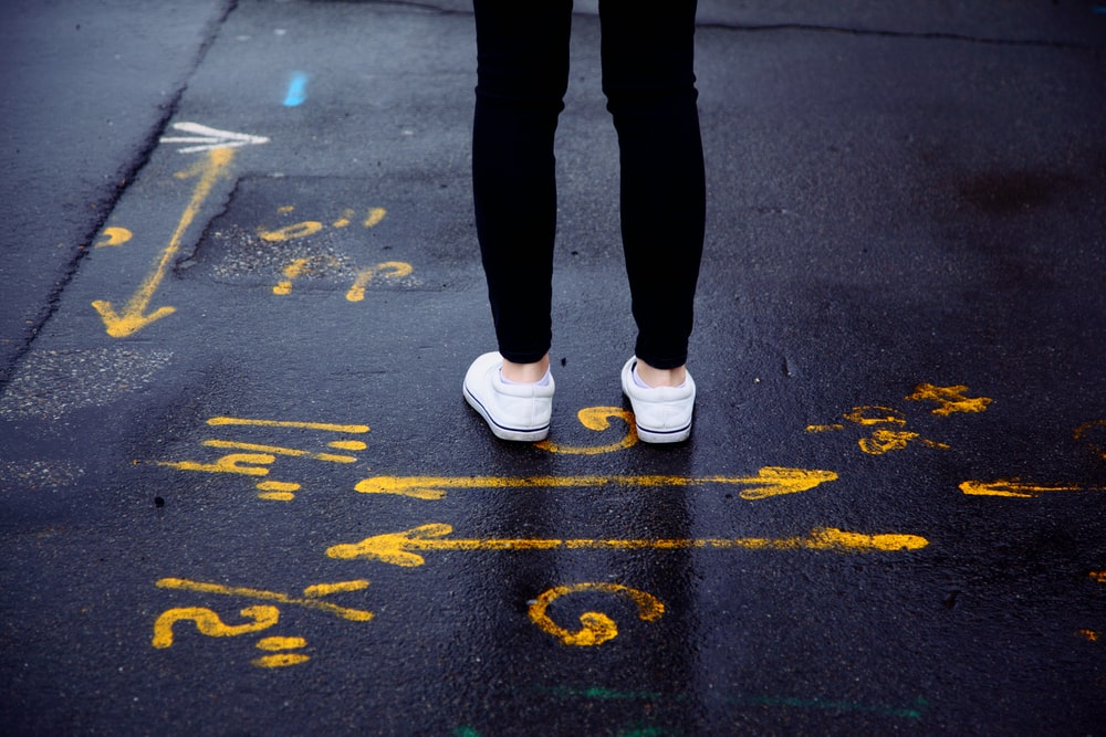 person in black pants and white sneakers standing on black asphalt road