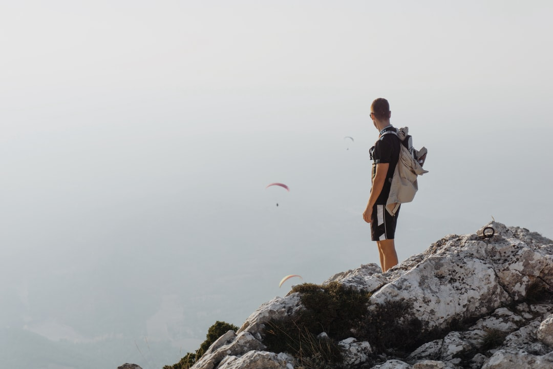 A man at the top of mountain watching three paragliders