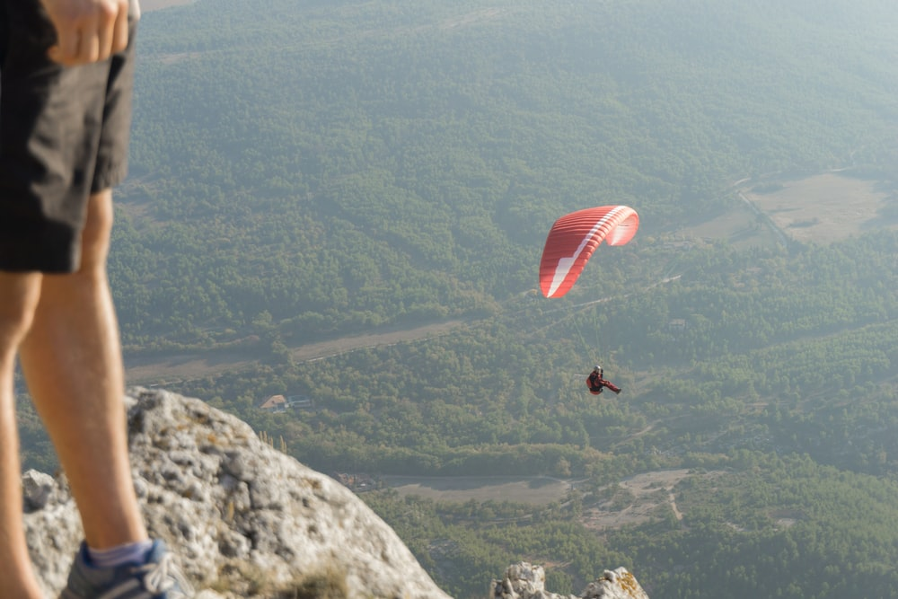 person in black jacket riding red parachute over green mountains during daytime
