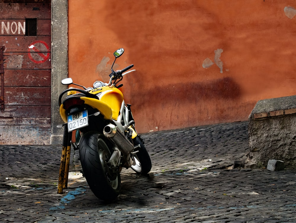 yellow and black motorcycle parked beside orange wall