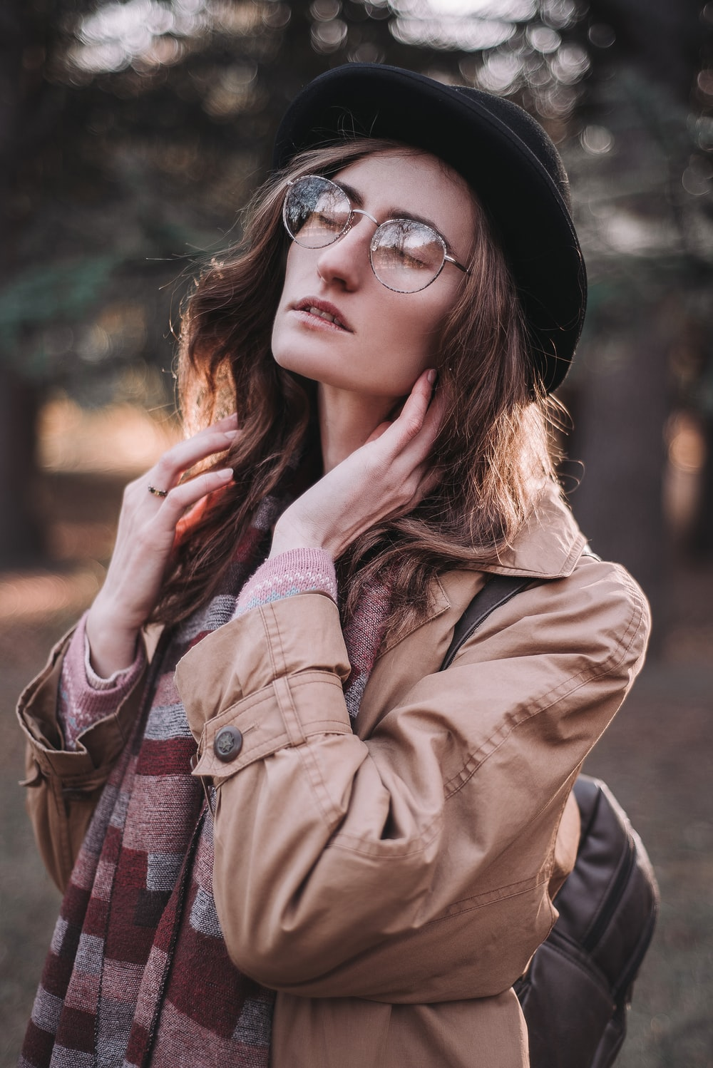 woman in brown leather jacket wearing black sunglasses