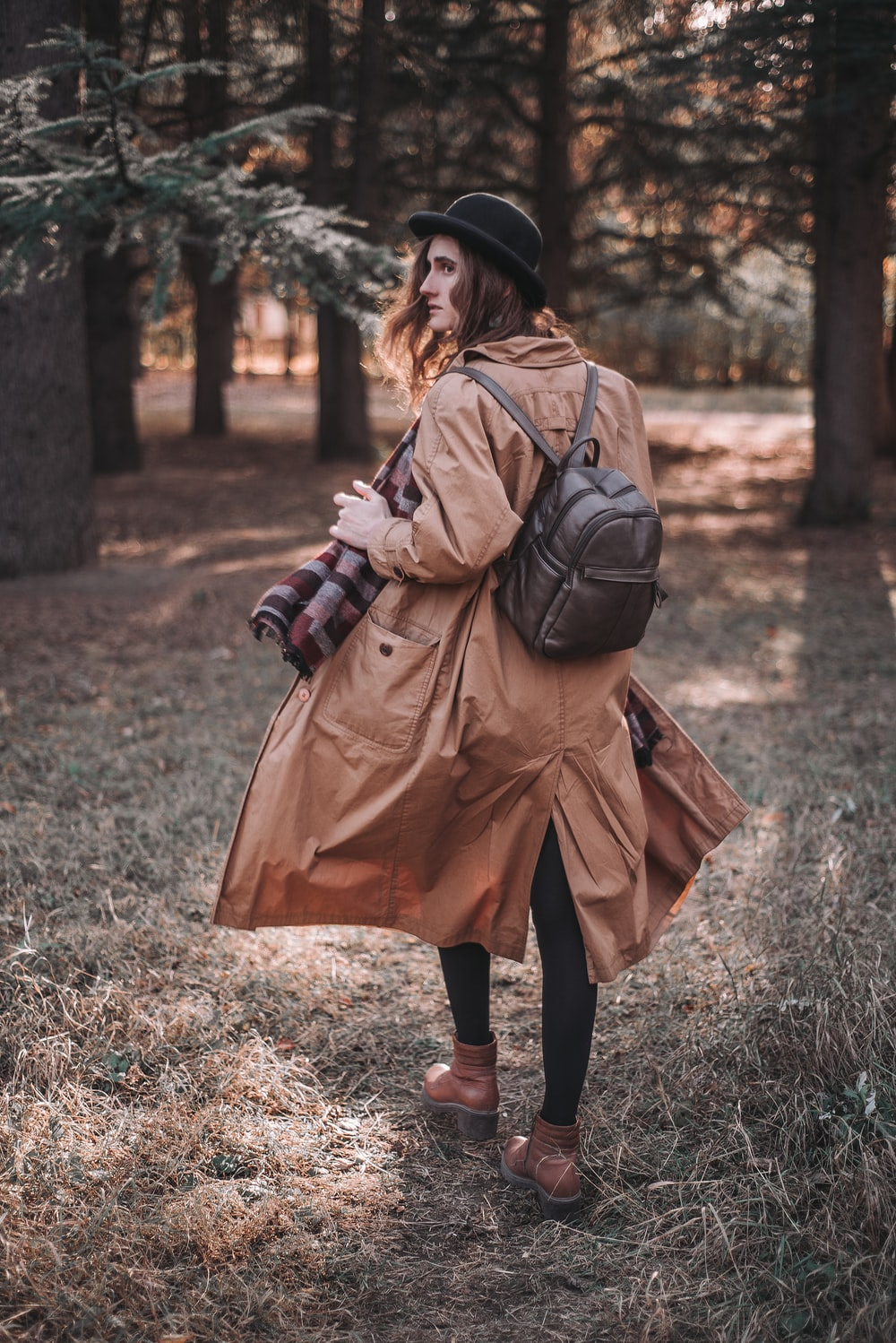 woman in brown coat and black boots walking on green grass field during daytime